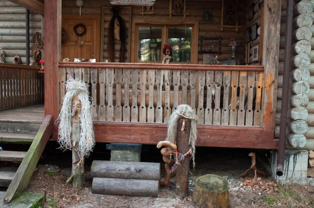 old log house with creepy wood statue