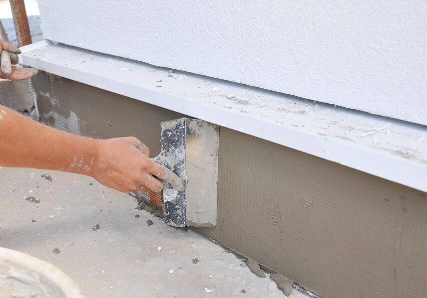 man plastering around the house's foundation